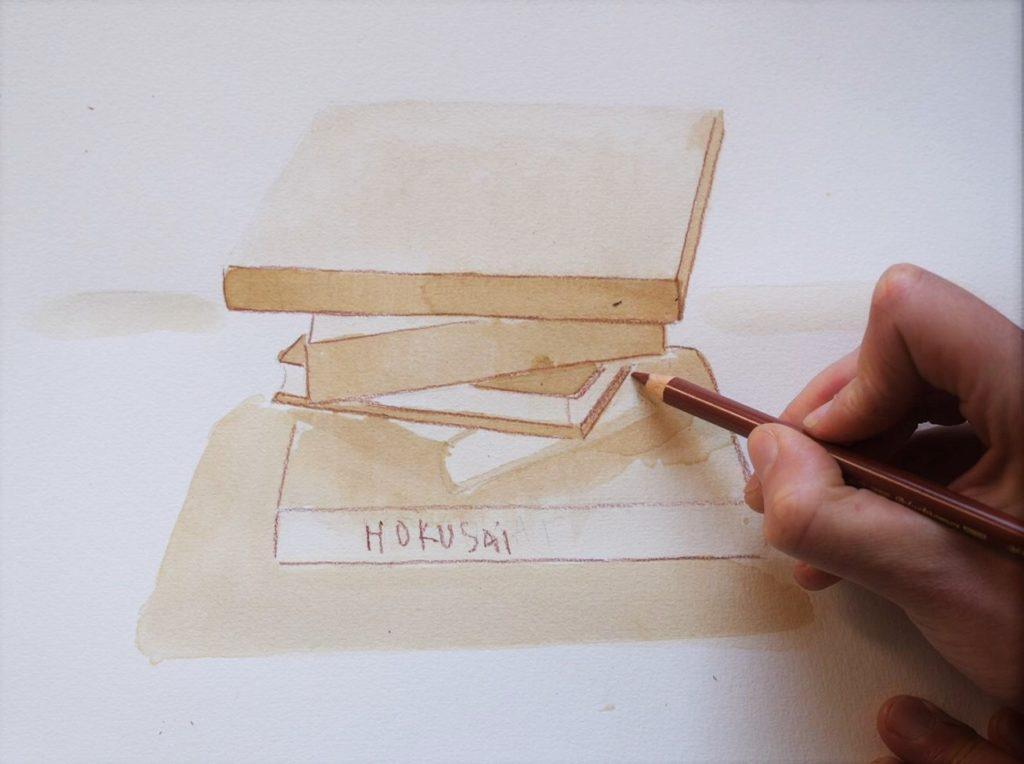 dessiner-en-perspective-une-pile-de-livres-placement-ombrages-thé-noir-et-crayon-de-couleur